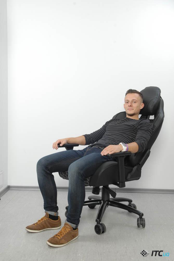 Человек в кресле Hator Icon Tracer с откинутой спинкой на половину